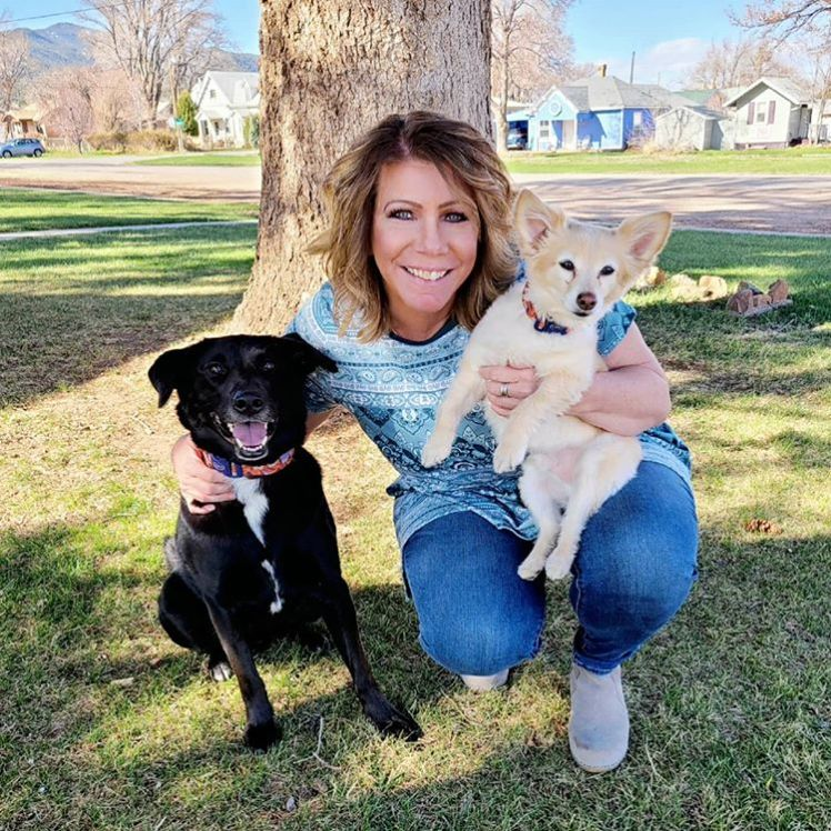 Meri Brown posing with two dogs