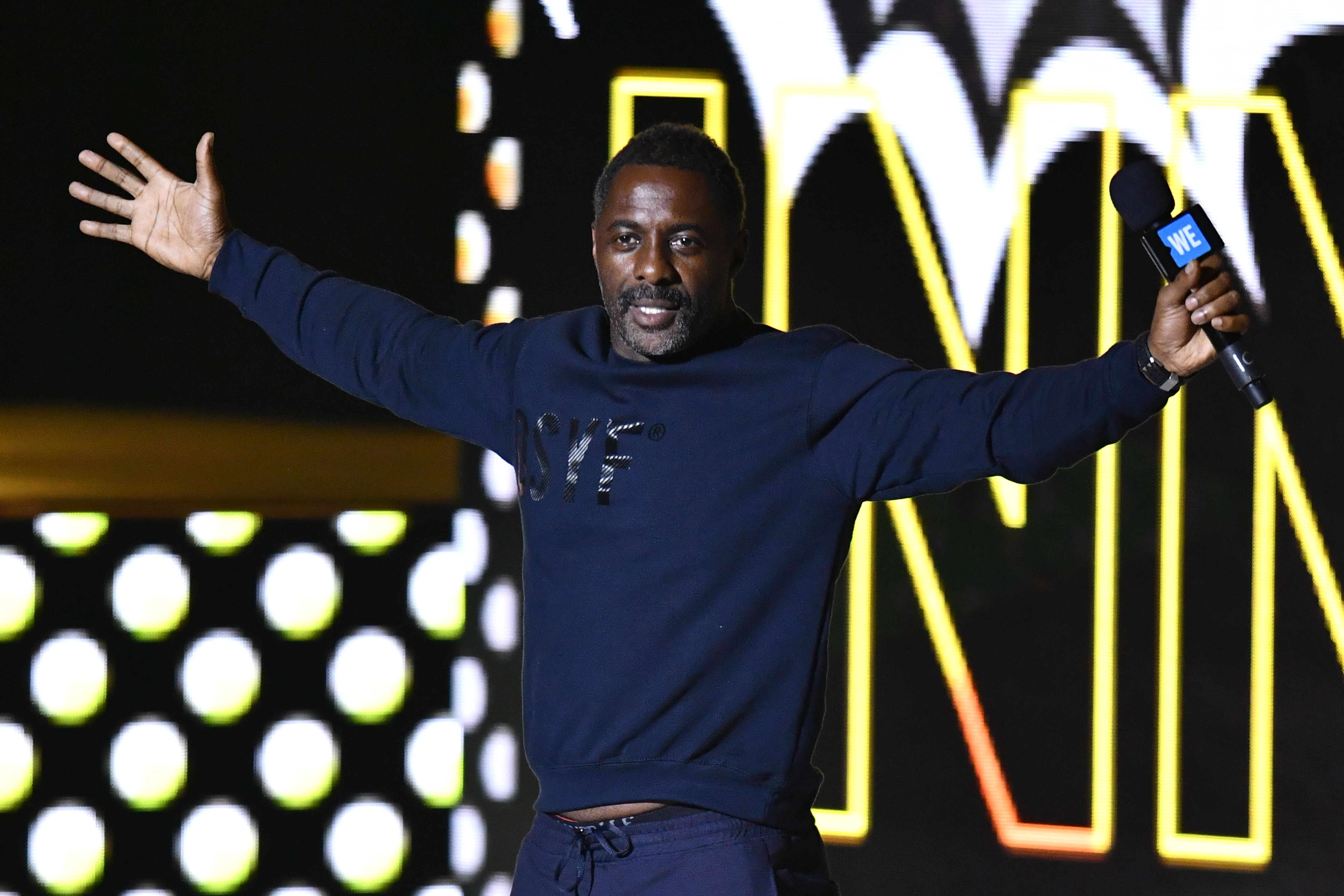 Idris Elba stretches his arms out while holding a microphone
