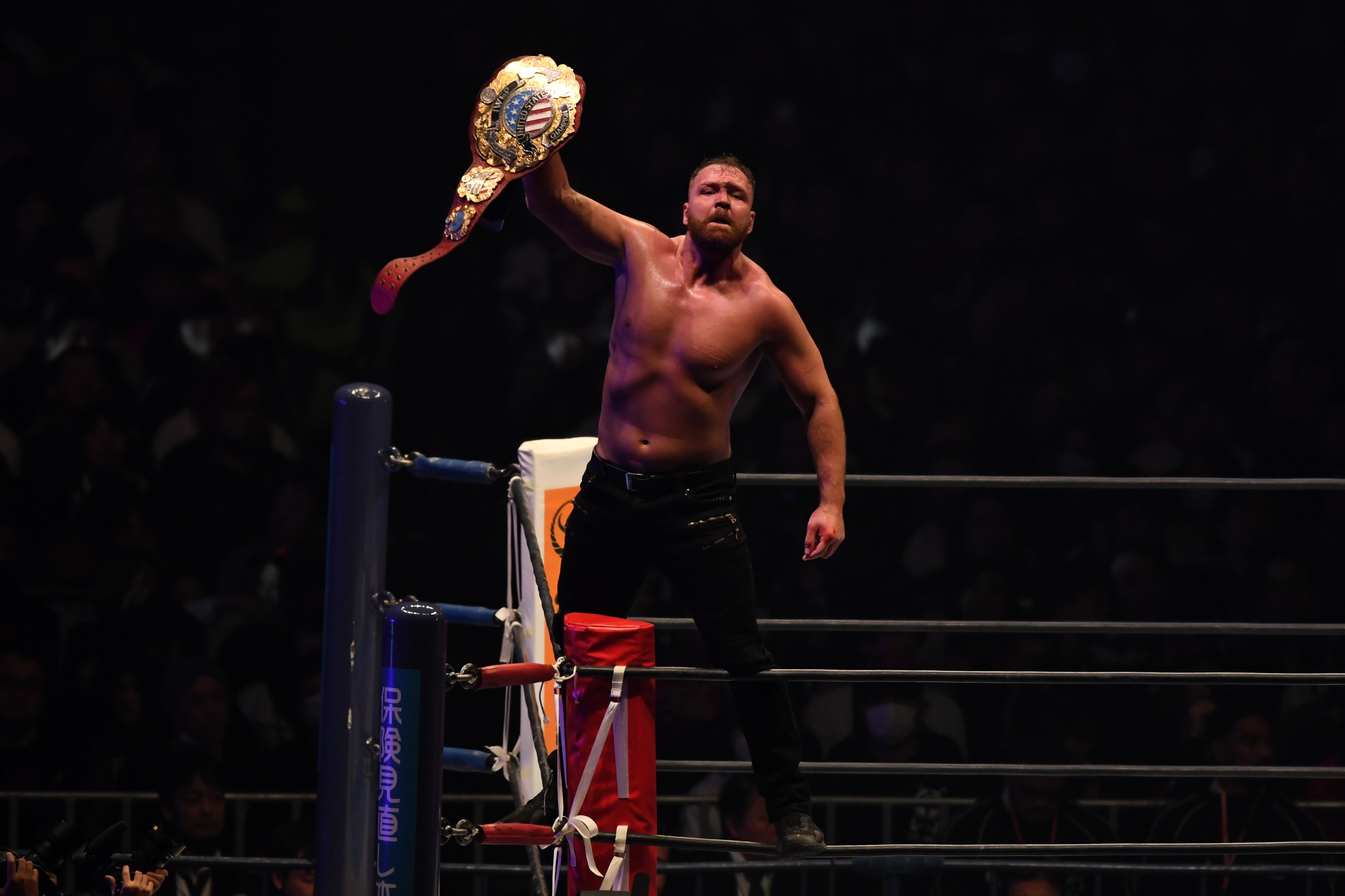 Jon Moxley holdling up the IWGP United States Heavyweight Championship