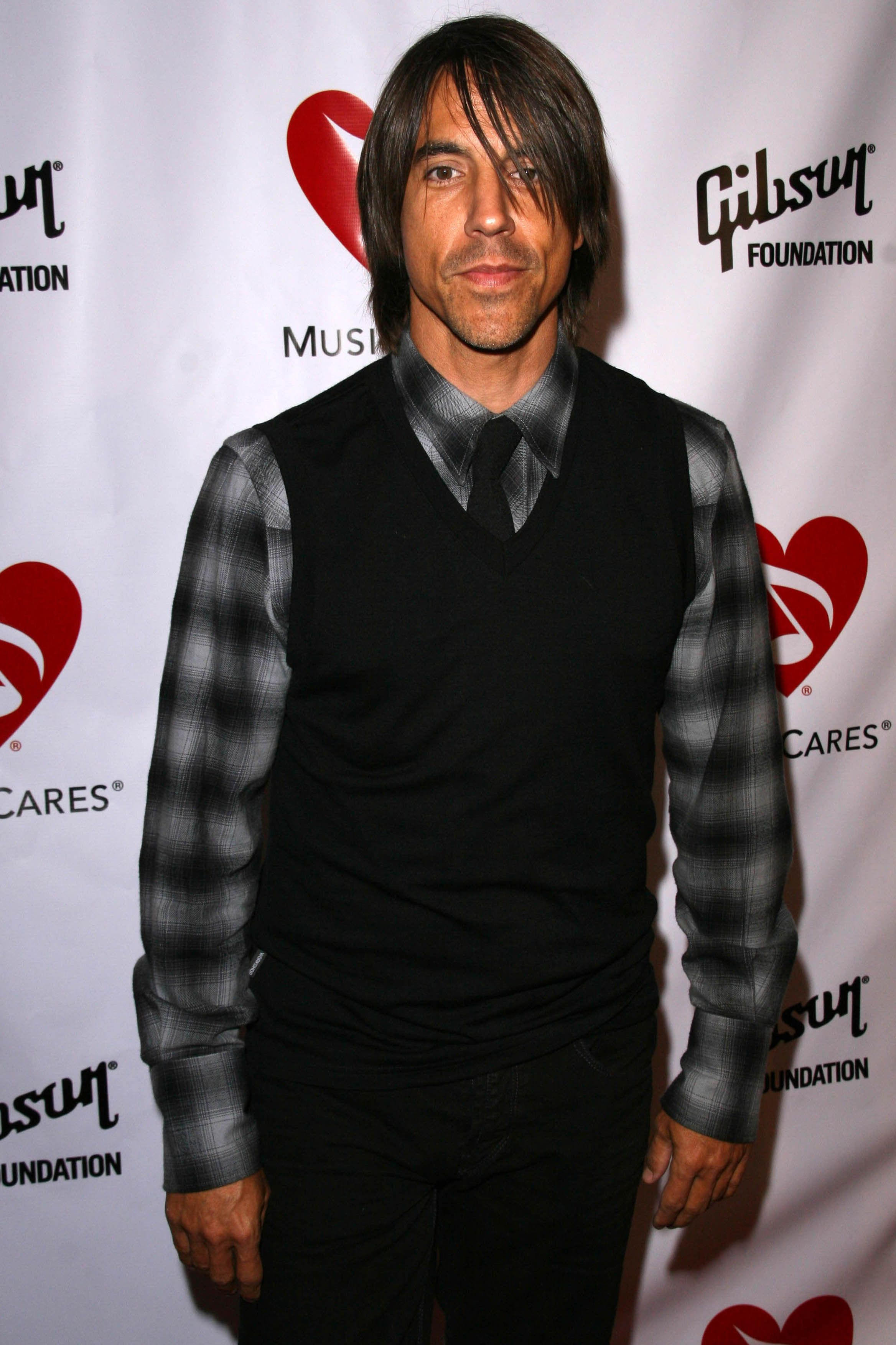 Anthony Kiedis wears a black sweater vest and gray plaid shirt at an event.