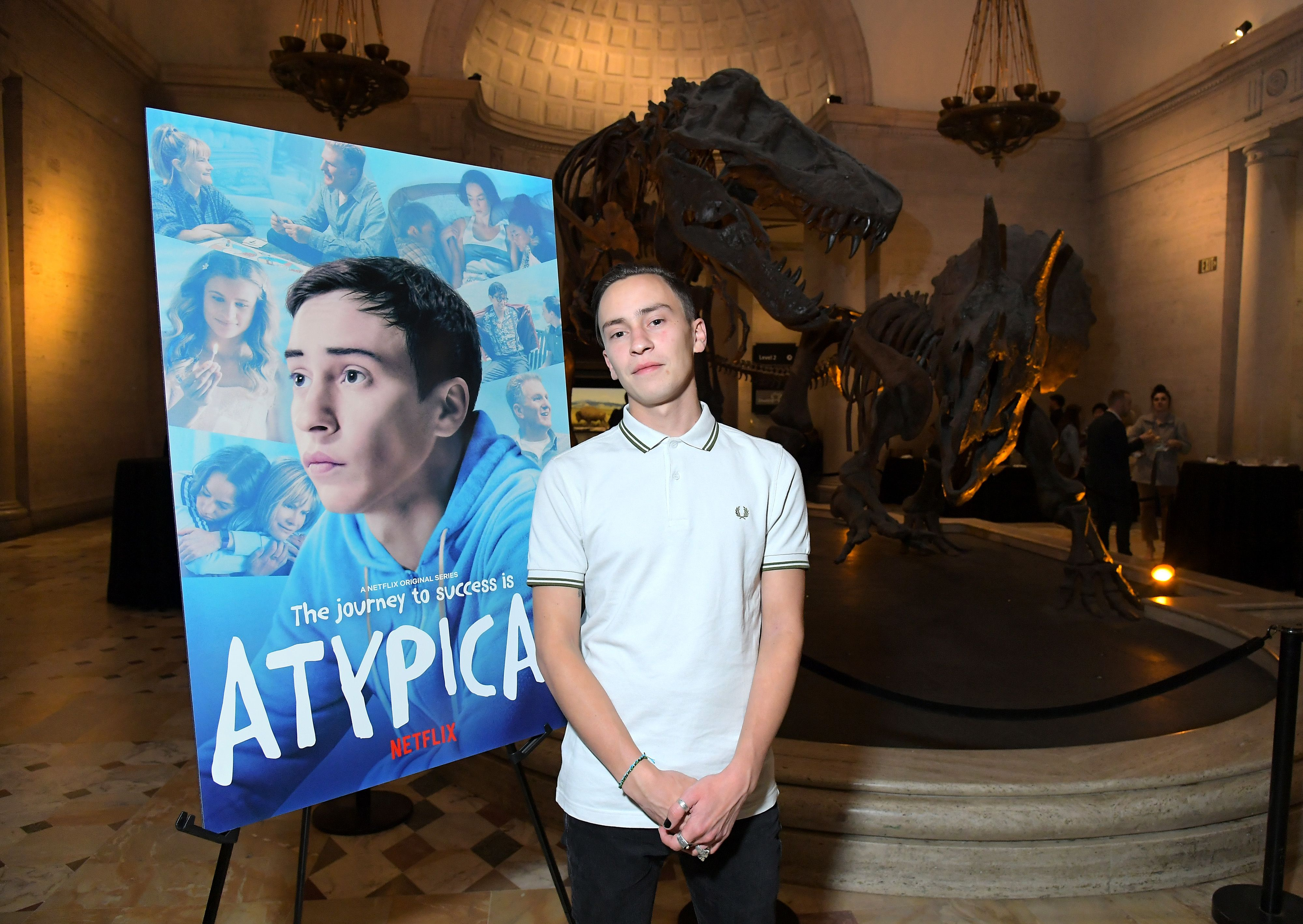 Keir Gilchrist stands in a white shirt next to an 'Atypical' sign.