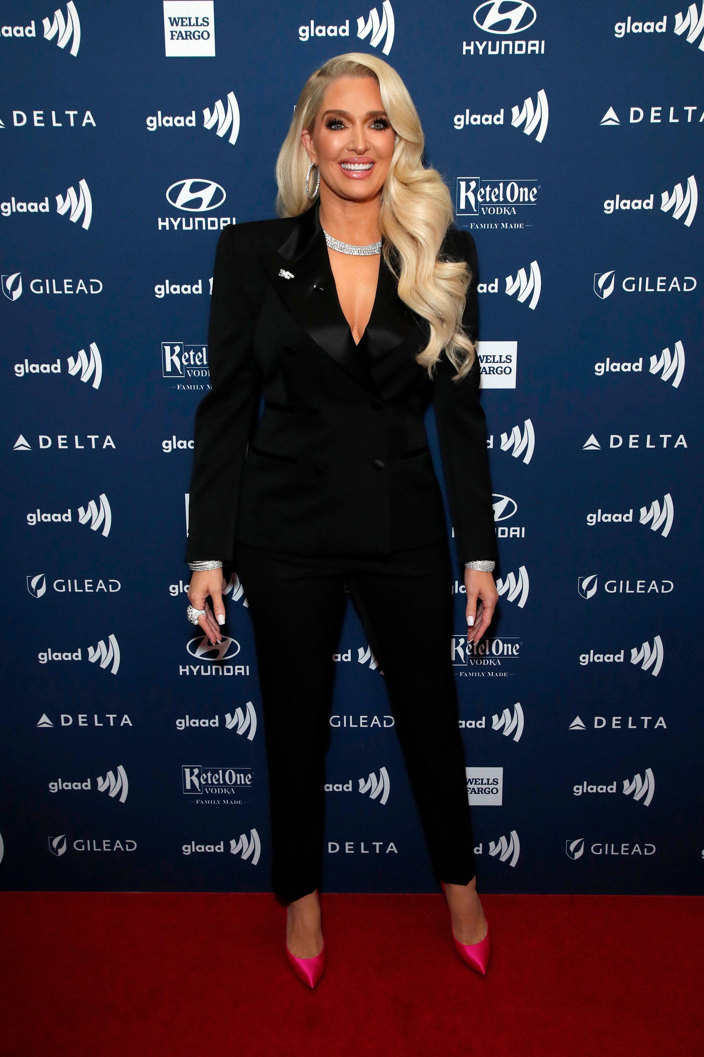 Erika Jayne wears a black pantsuit.
