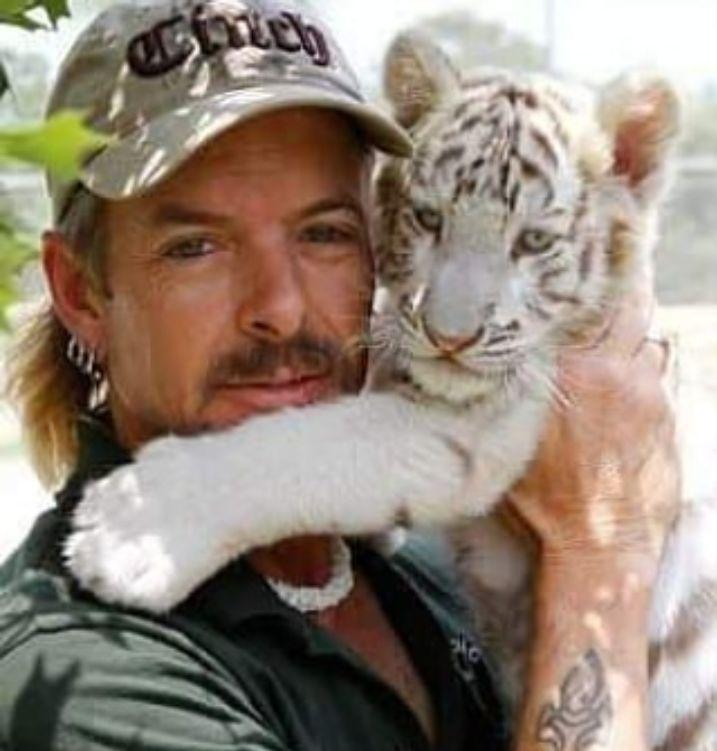 Joe Exotic holding white tiger