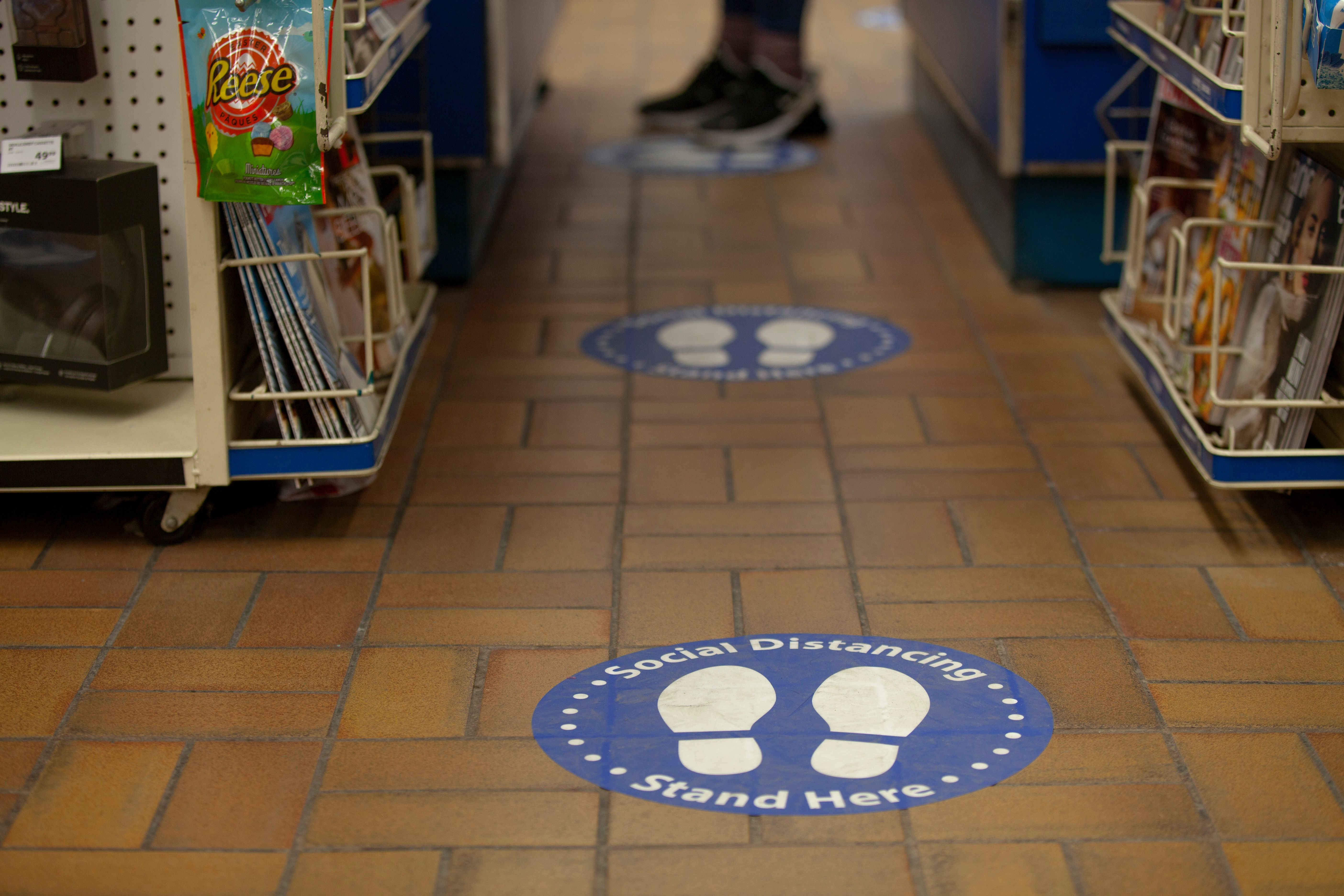Grocery store floor with sign showing people where to stand to maintain social distancing