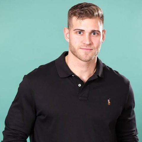 Luke P. poses against a Tiffany colored background