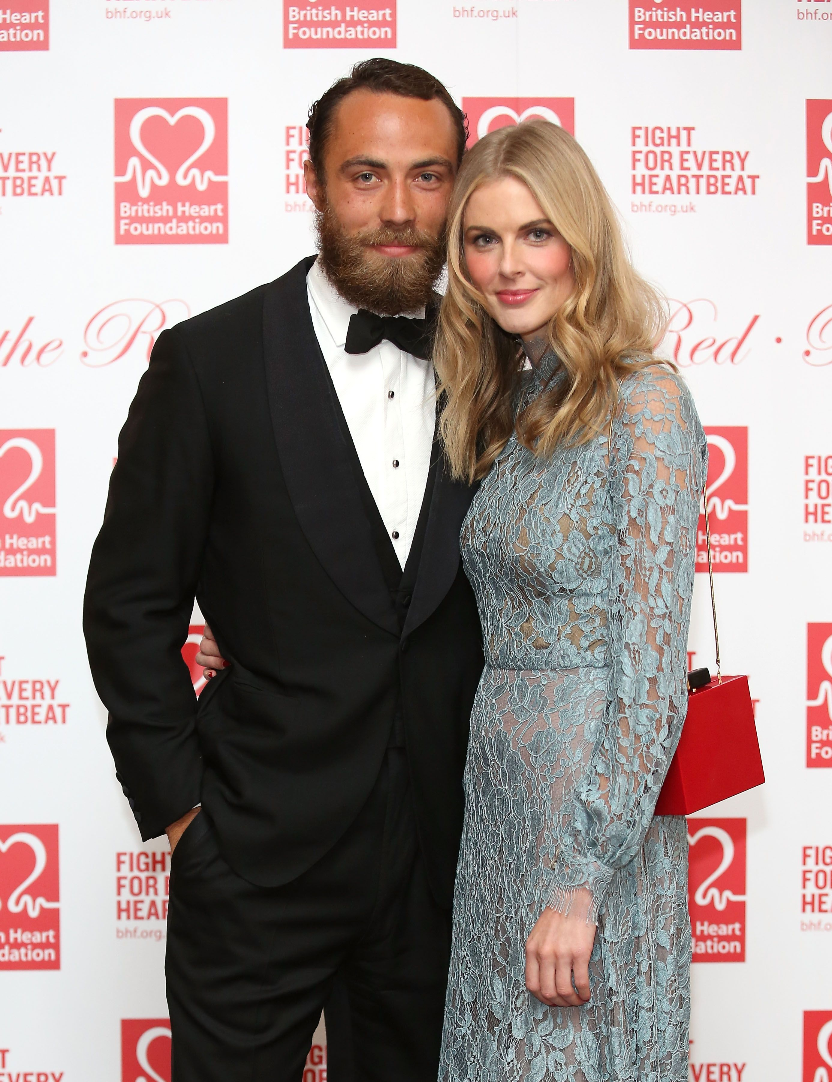 James Middleton and Alizee Thevenet cuddle while standing as they pose for the camera.