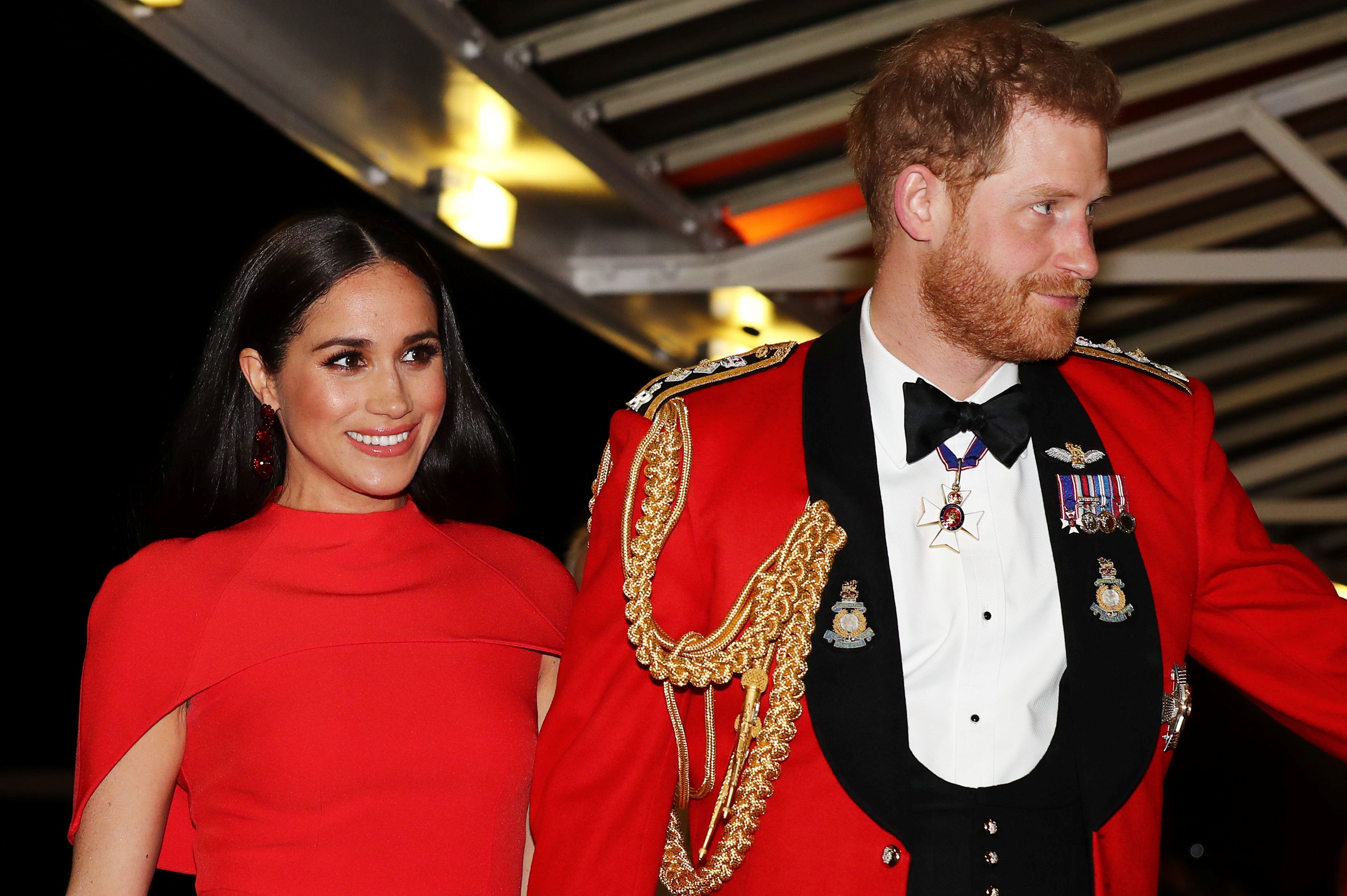 Meghan and Harry in red outfits as they attend an event during their farewell tour