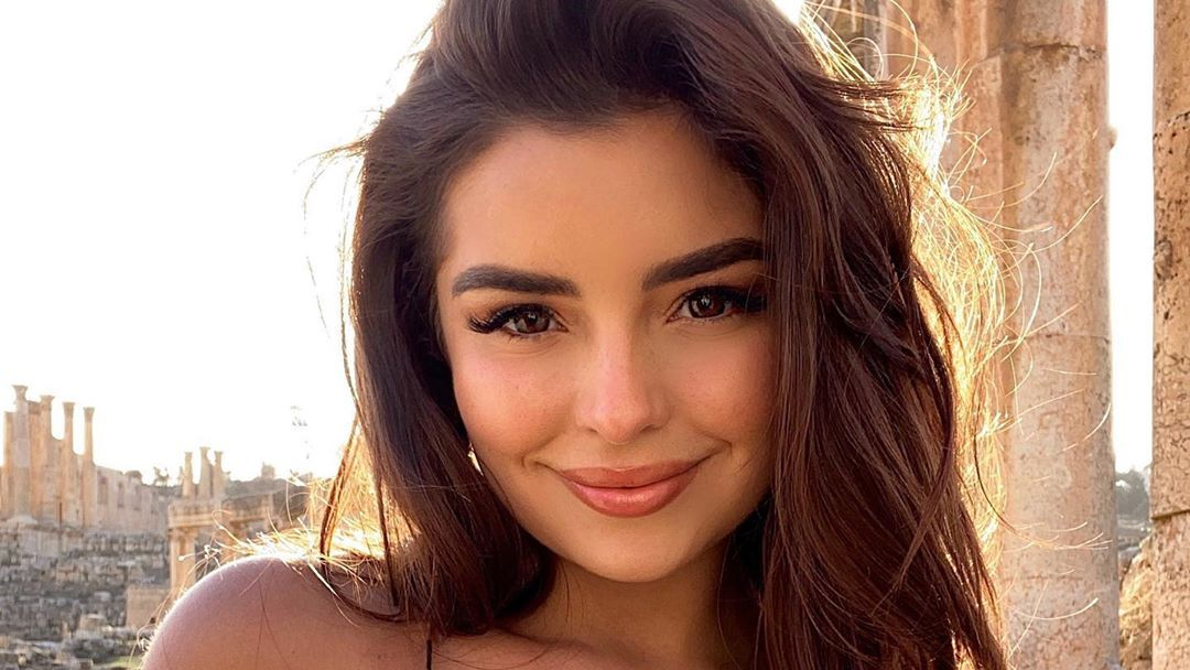 Demi Rose poses smiling outdoors