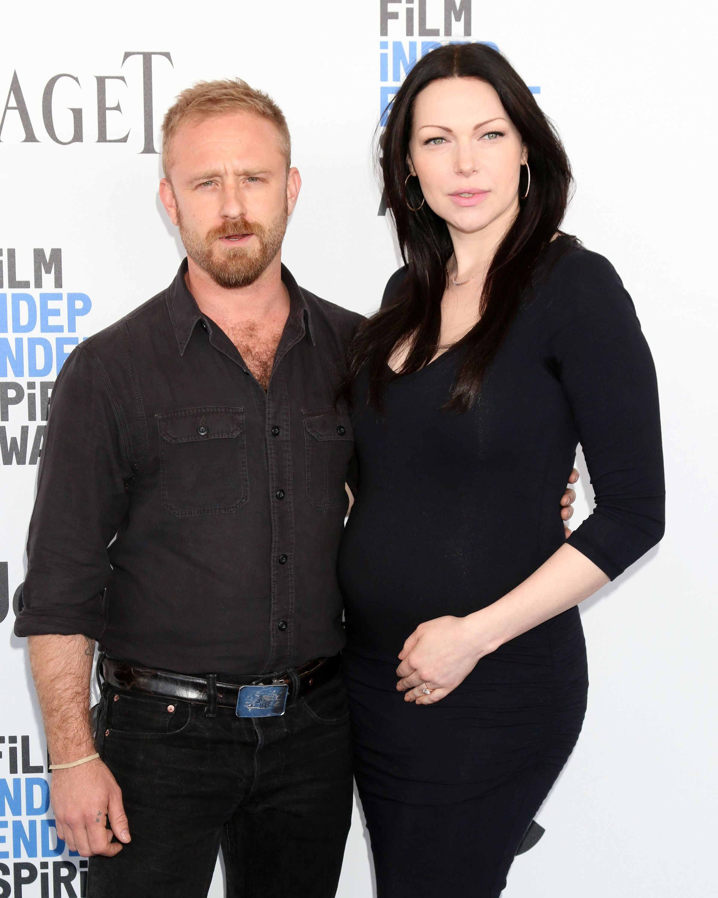 Ben Foster and a pregnant Laura Prepon pose together at an event.