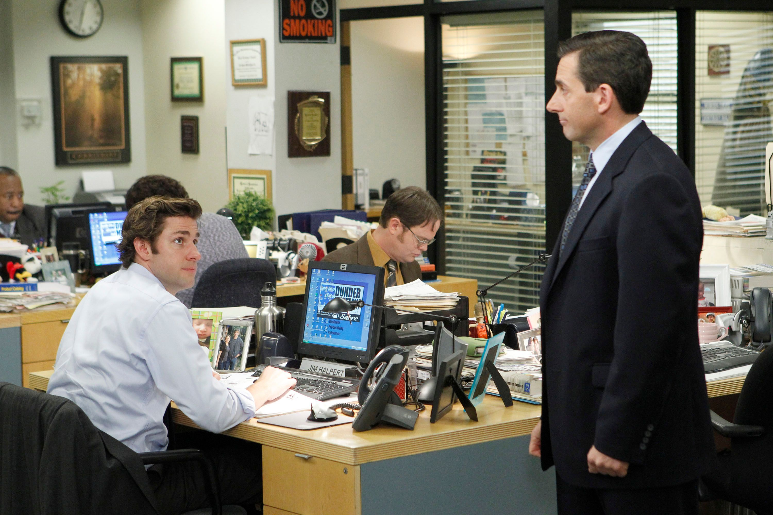 Steve Carell stands by John Krasinski where he sits at his desk on the set of The Office