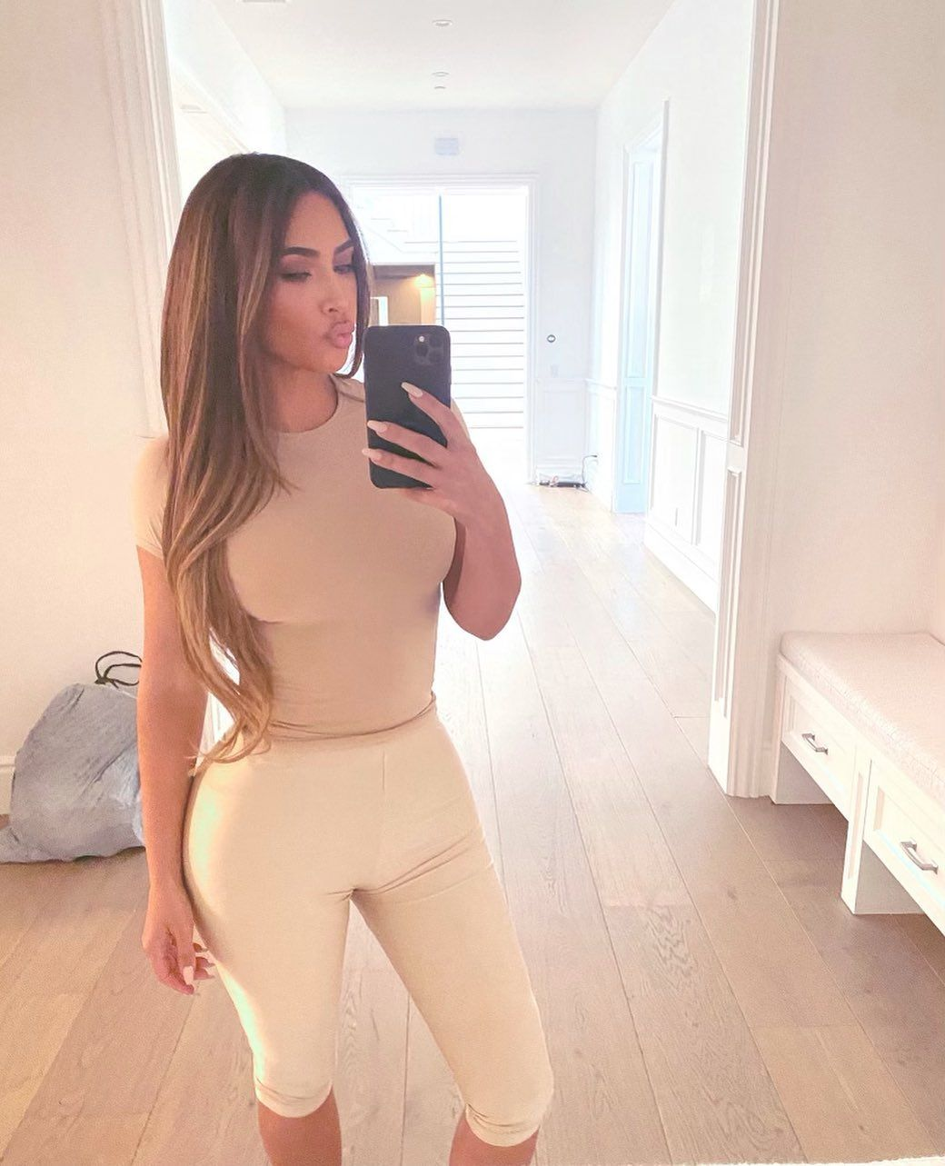 A photo of Kim Kardashian taking a phone selfie in a white pant and brown blouse.