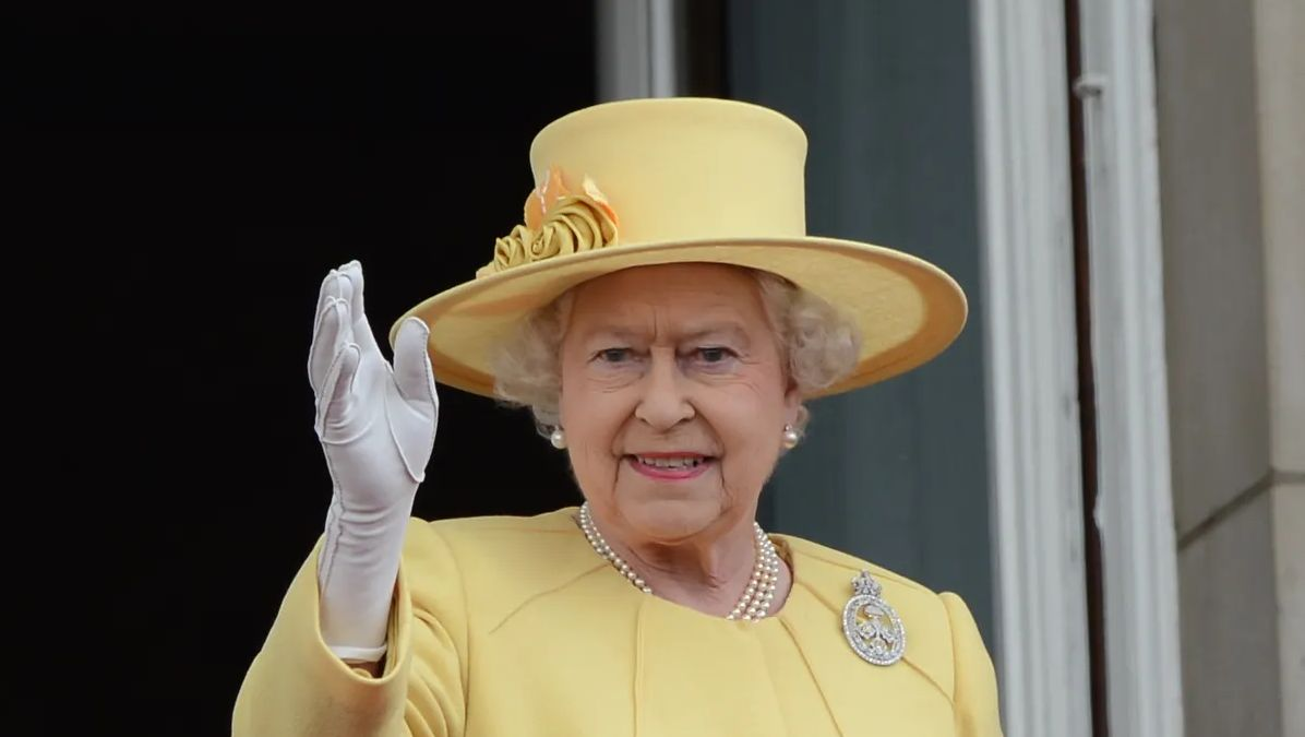Queen Elizabeth II wearing a yellow outfit with a hat while waving at the crowd.