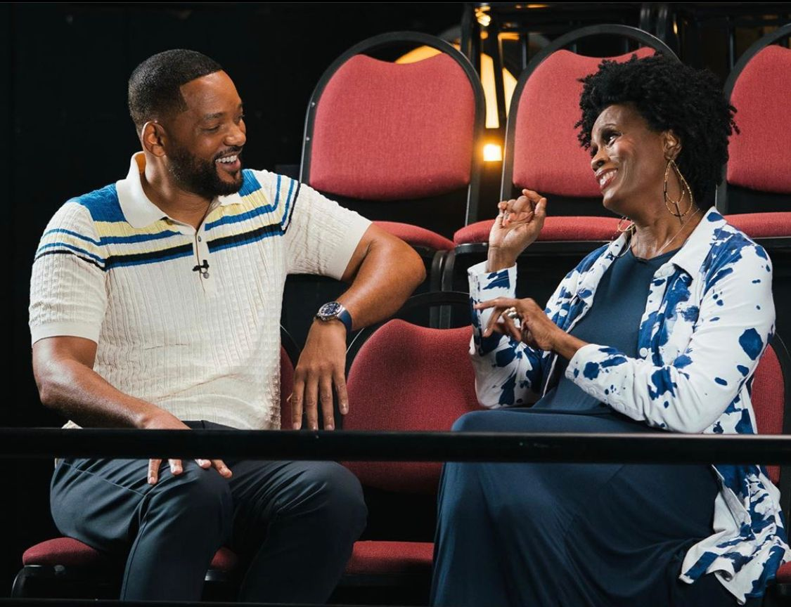 A photo showing Will Smith and Janet Hubert conversing with huge smiles on their faces.