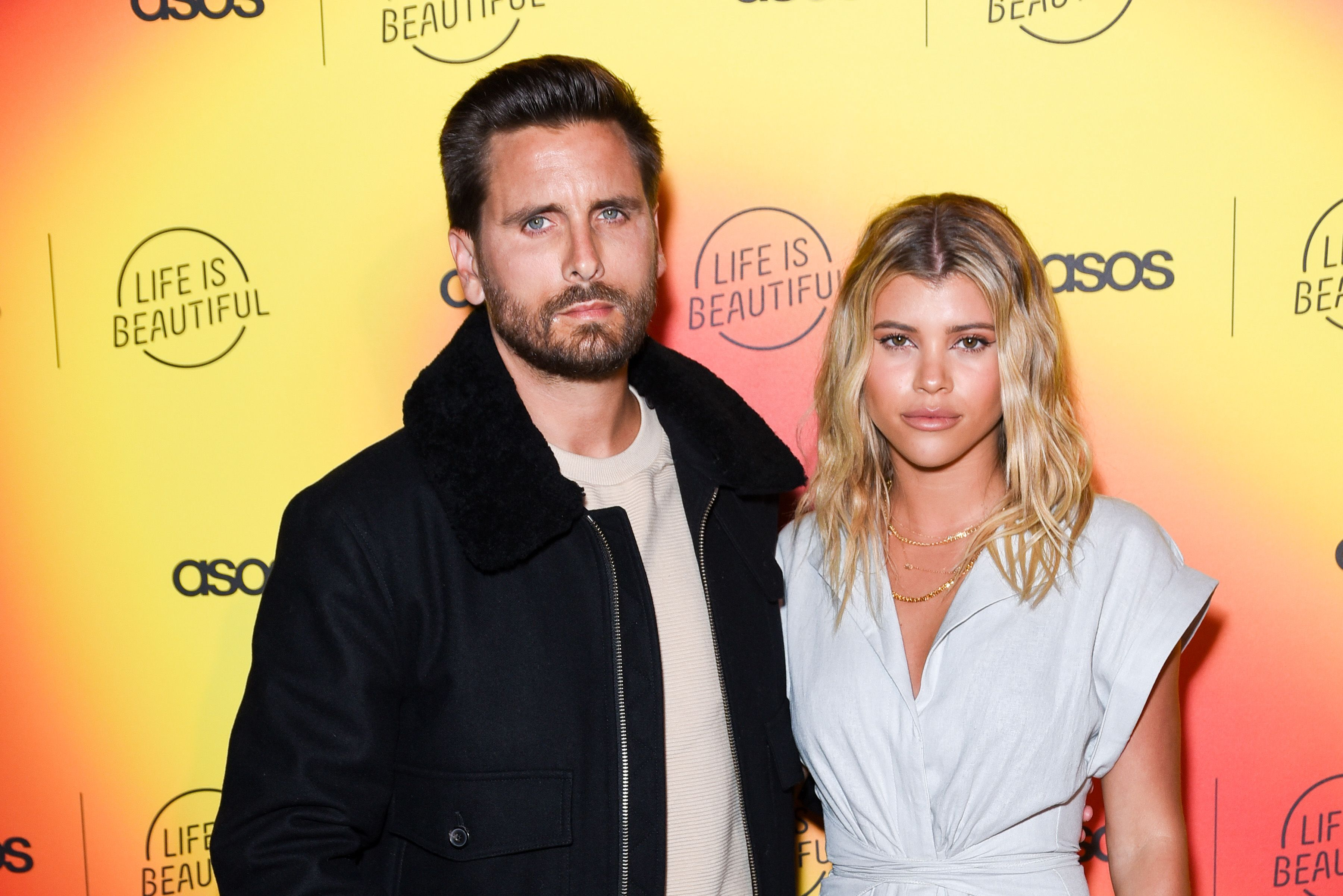 Scott Disick and Sofia Richie smiling against a yellow and orange backdrop.