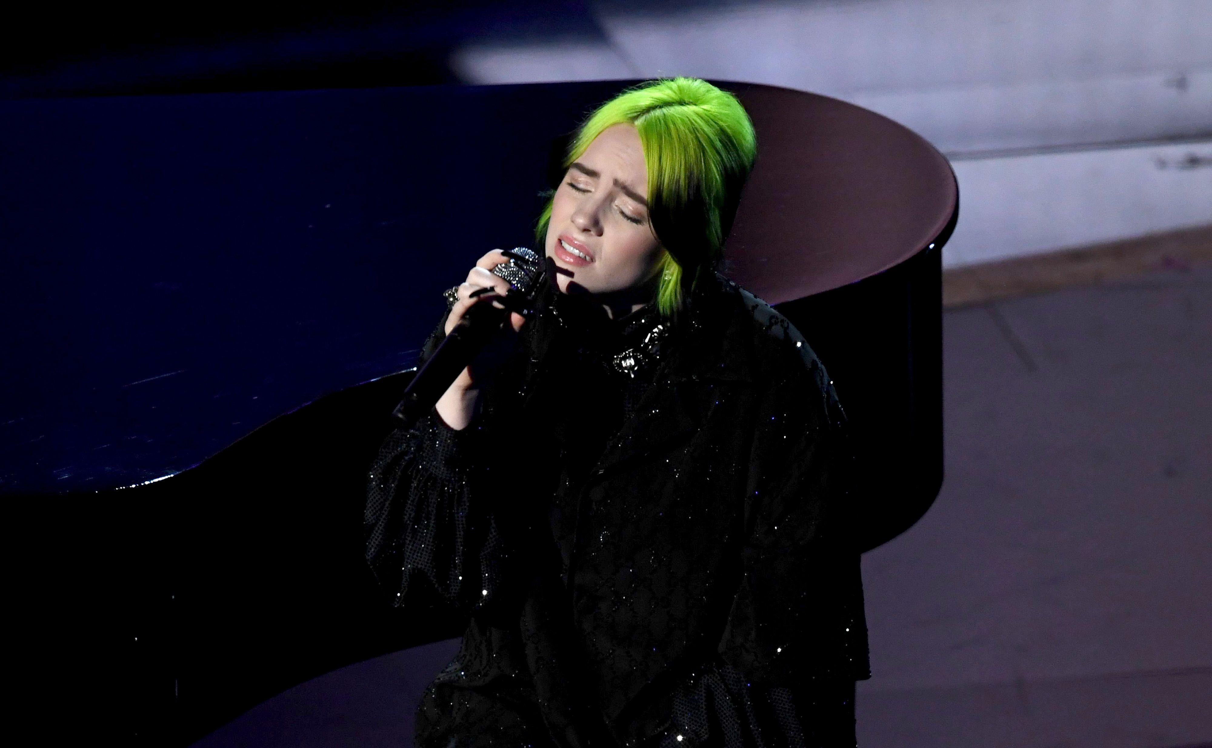 Billie Eilish singing on stage.