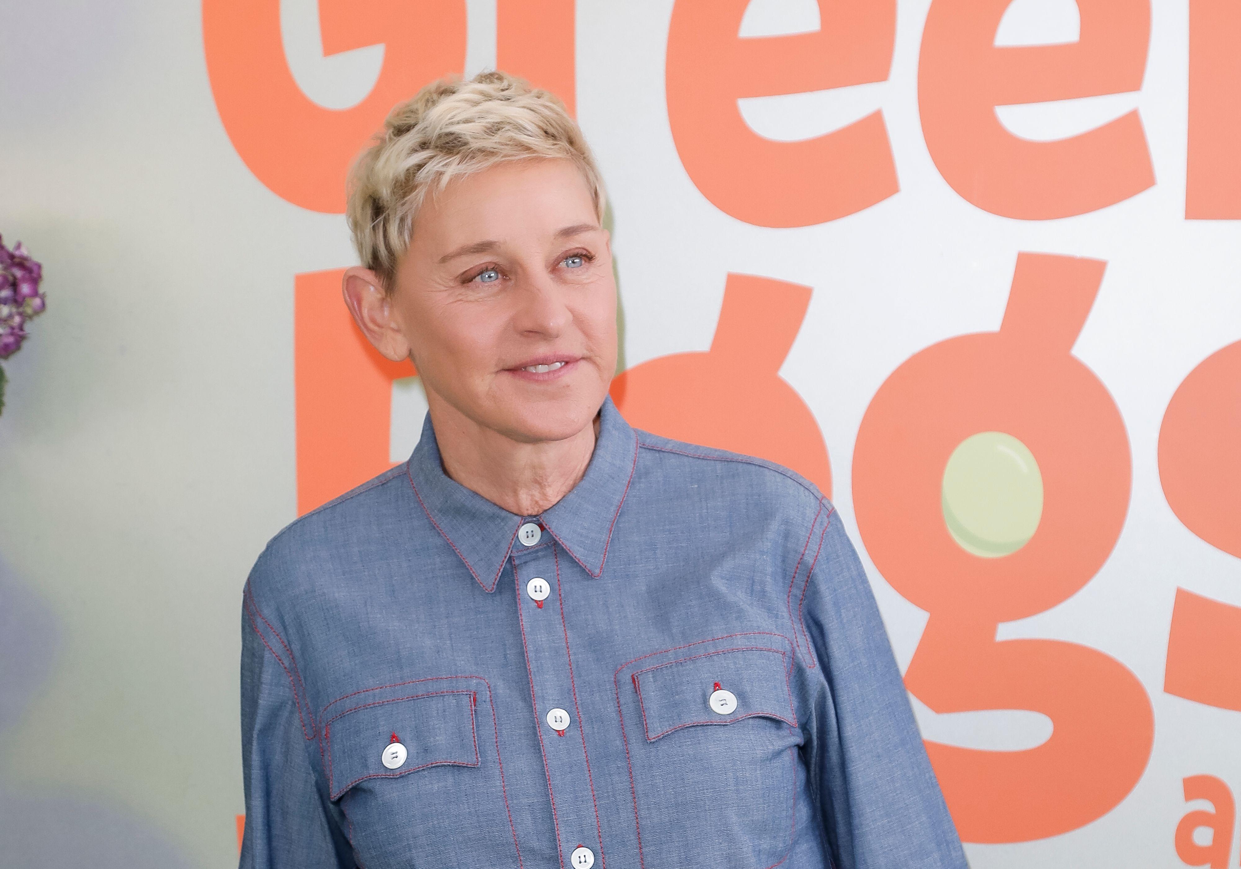 Ellen DeGeneres poses in front of a wall