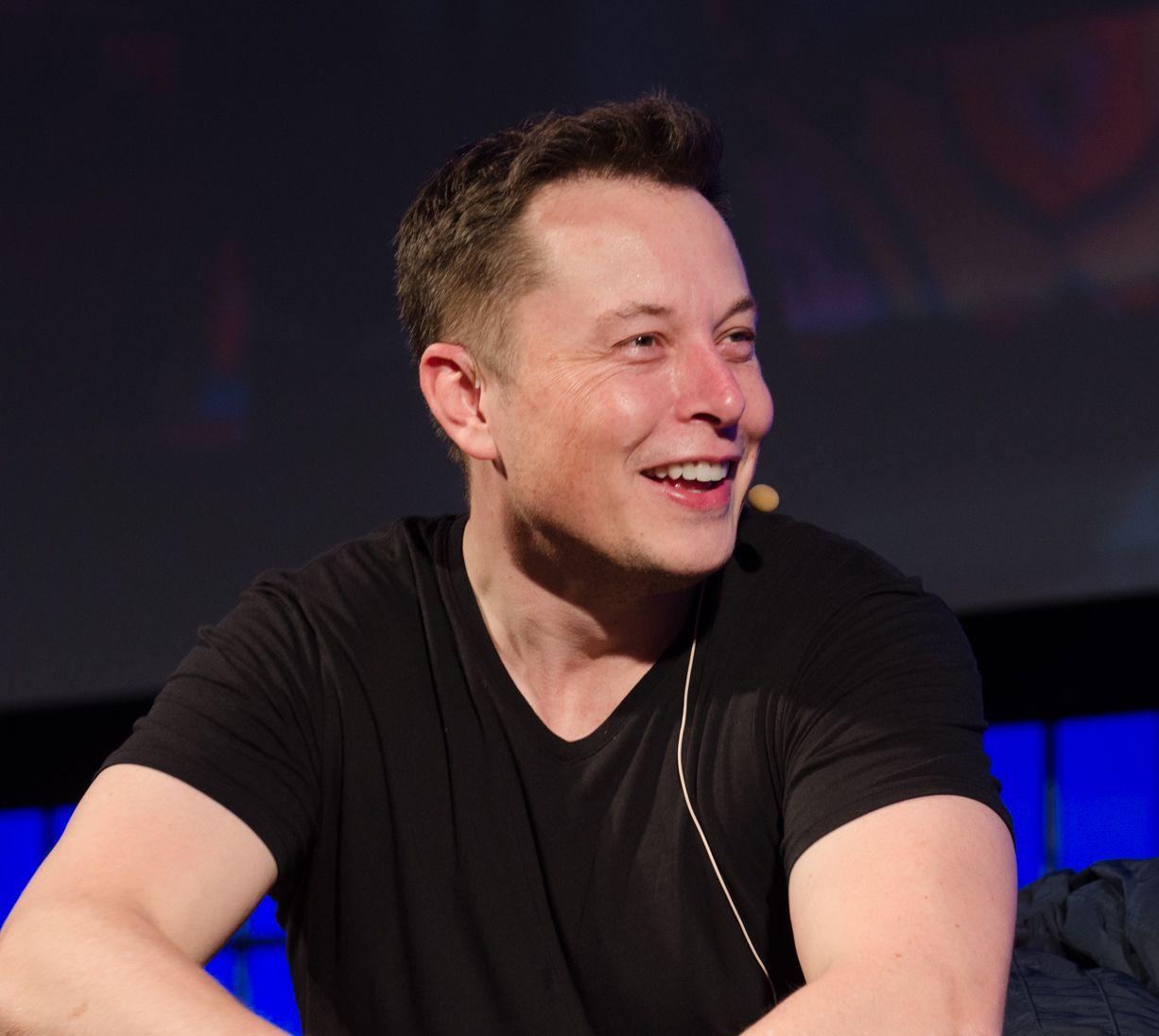 Elon Musk wearing a black t-shirt.