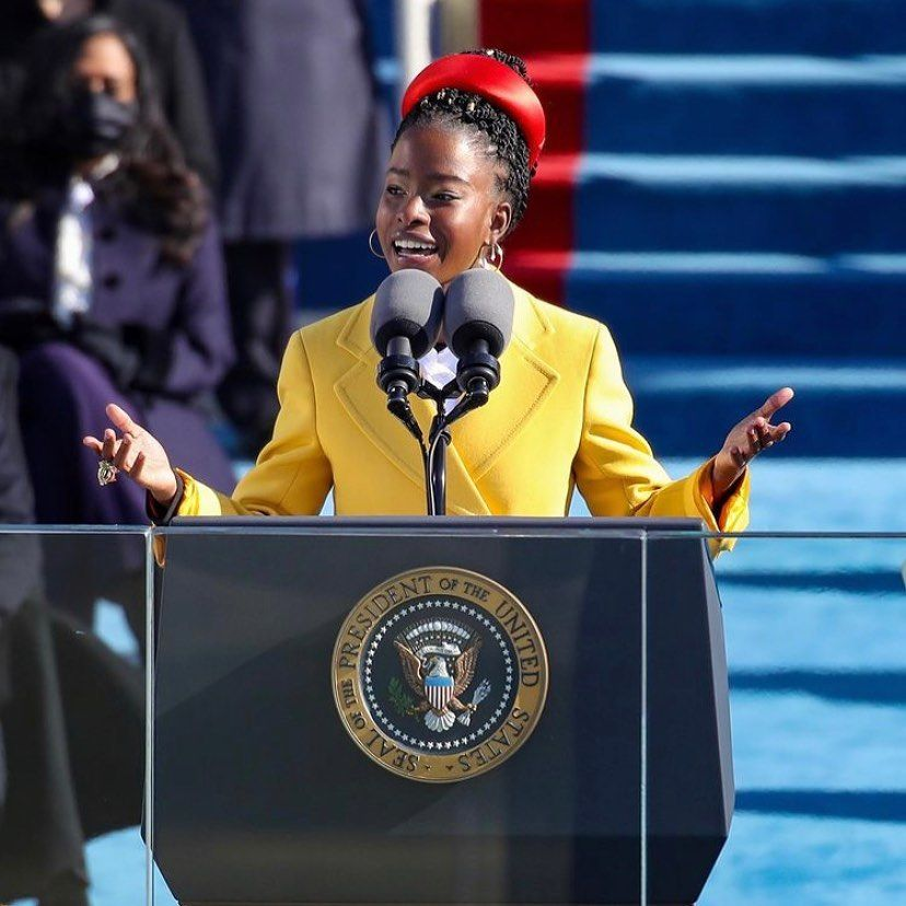 A photo of Amanda Gorman giving a speech at President Biden's inaugural ceremony in a yellow jacket dress and red band on her hair.