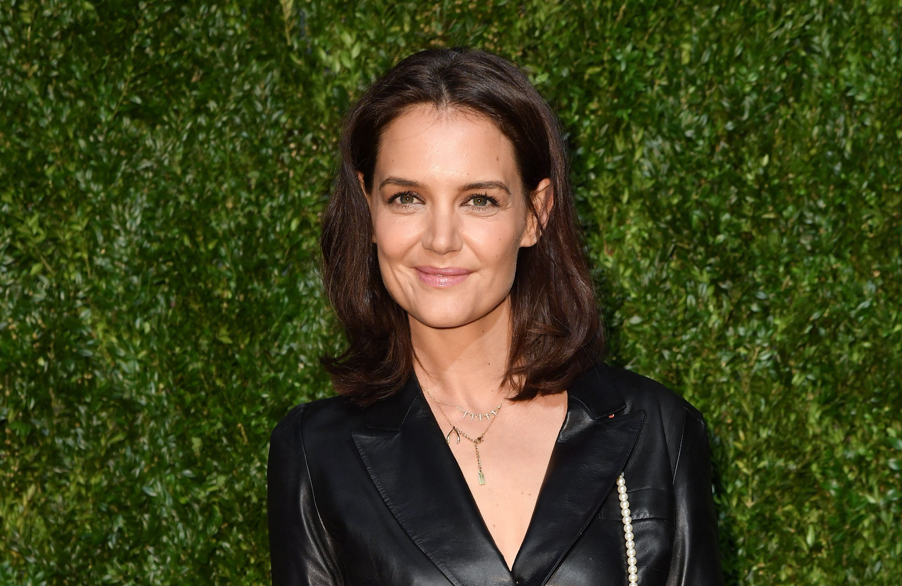 Katie Holmes posing in front of grass bush.