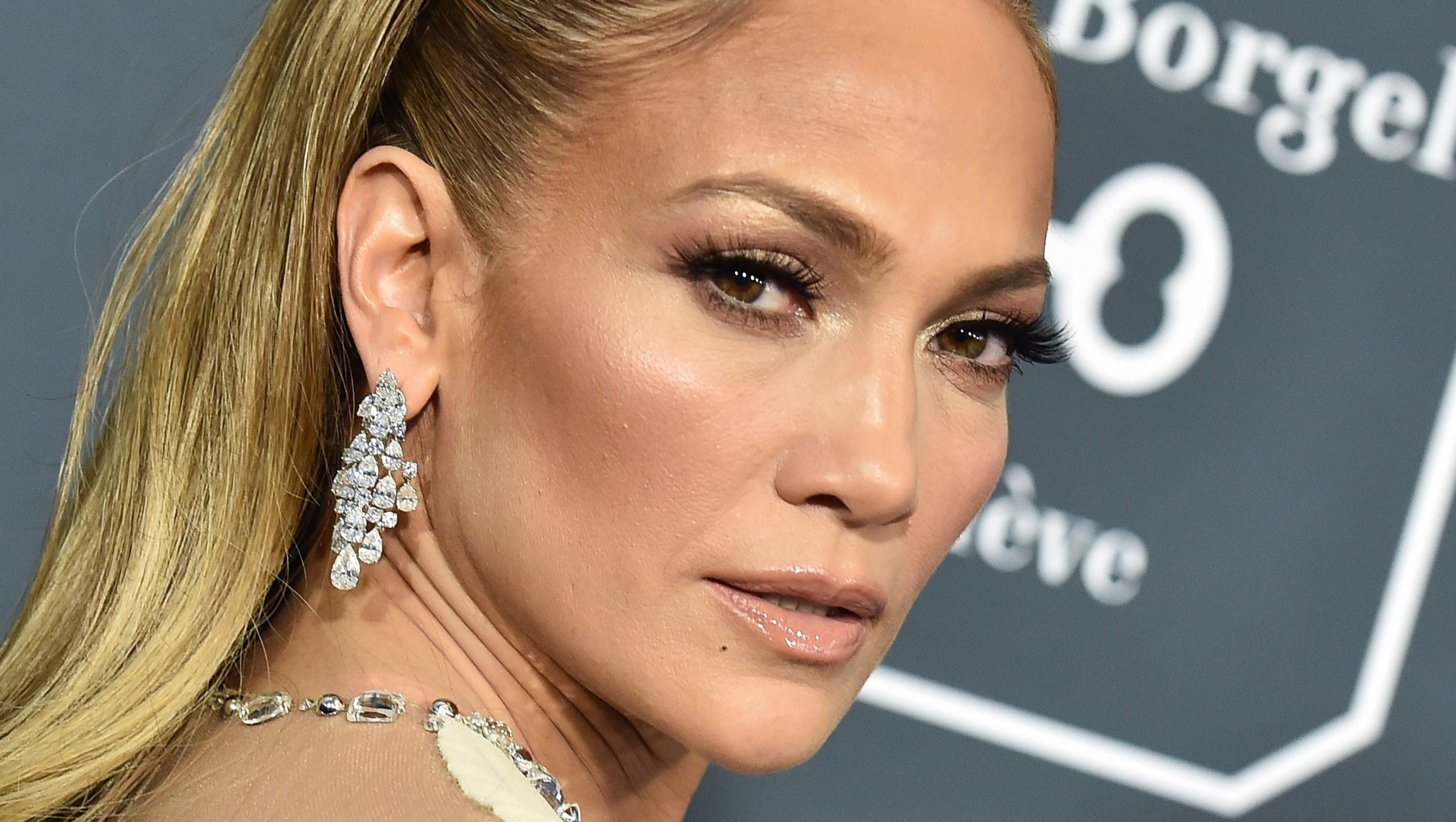 Jennifer Lopez looks over her shoulder with dangling diamond earrings.