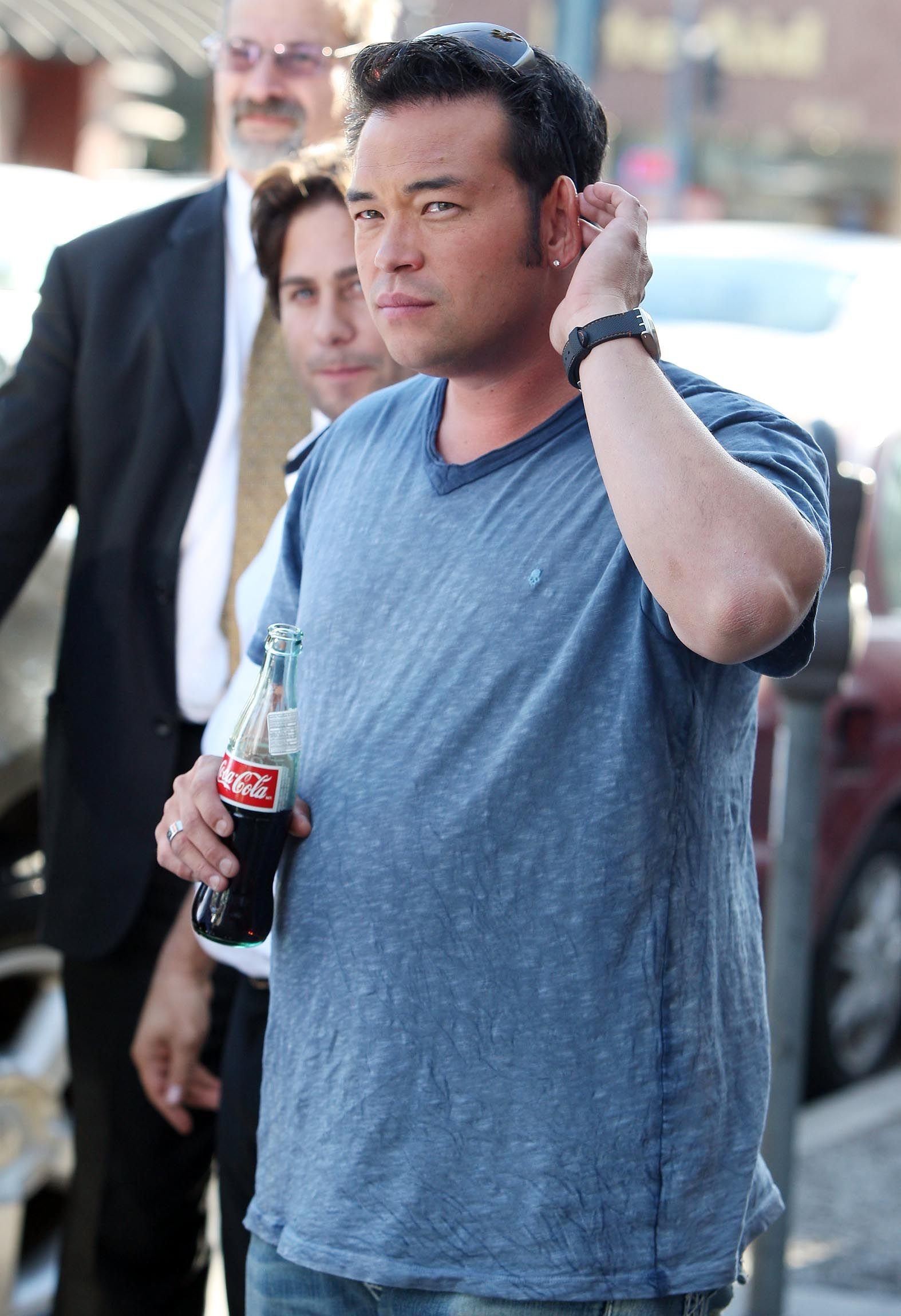 A photo showing Jon Gosselin sporting a plain shirt with denim pant and holding a bottle of coca-cola