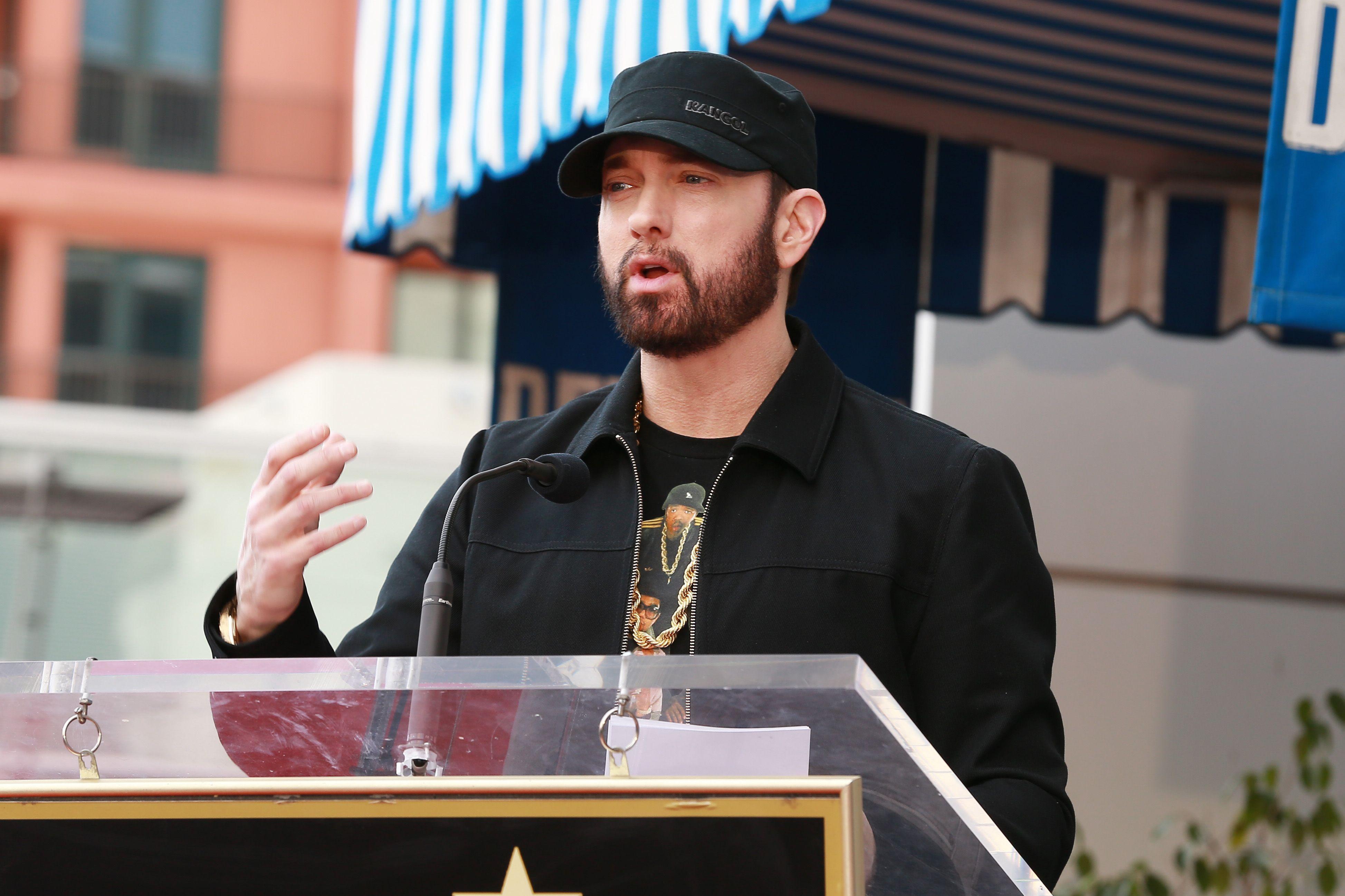 Eminem speaks at a podium